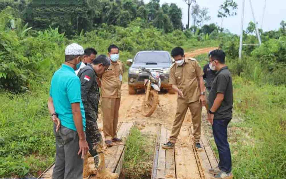 Bupati Barito Utara, H Nadalsyah didampingi sejumlah pegawai meninjau salah satu jembatan yang perlu diperbaiki.