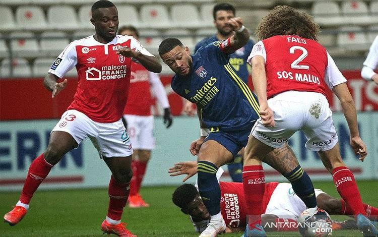 Kapten Olympique Lyon Memphis Depay (tengah) dikawal ketat setidaknya tiga pemain Reims dalam lanjutan Liga Prancis di Stadion Auguste-Delaune, Reims, Prancis, Jumat (12/3/2021) waktu setempat. (ANTARA/AFP/Francois Nascimbeni)