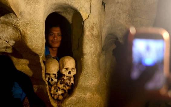 Wisatawan berfoto di antara tenggorak di tempat wisata kuburan gua batu Londa, Tana Toraja, Sulawesi Selatan, 1 Januari 2016. Pemakaman ini dipadati pengunjung pada liburan Tahun baru. (foto : TEMPO/Iqbal Lubis)