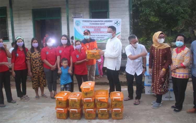 Bupati Lamandau, Hendra Lesmana didampingi Sekda dan Kadis Kesehatan saat seragkan bantuan untuk warga petarikan, Jumat 12 April 2021