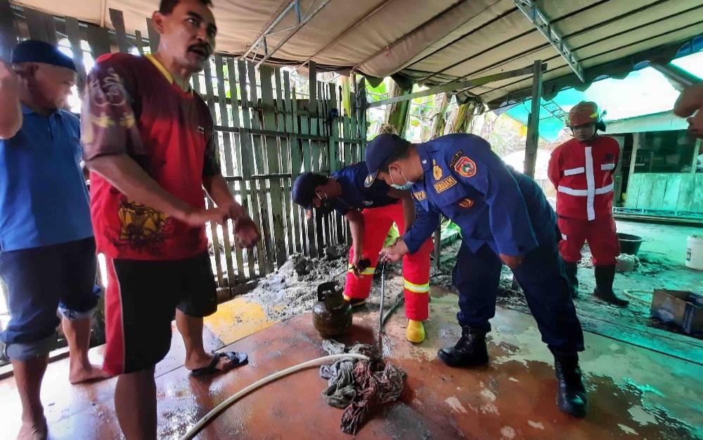 Petugas Damkar Kobar mengecek tabung gas 3 Kg yang bocor dan keluarkan api usai berhasil di padamkan