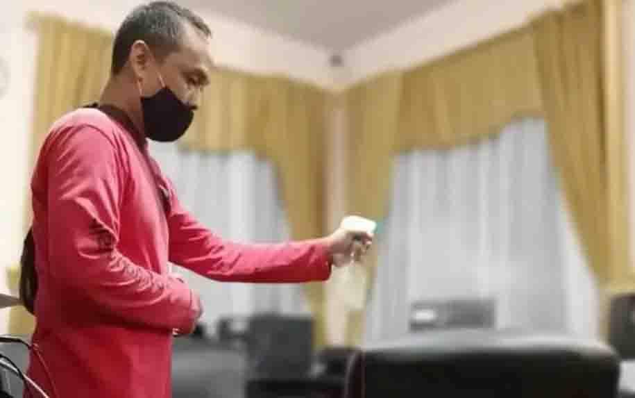 Salah satu pegawai Kemenag Kalteng saat menyemprotkan disinfektan di area perkantoran Kemenag Kalteng
