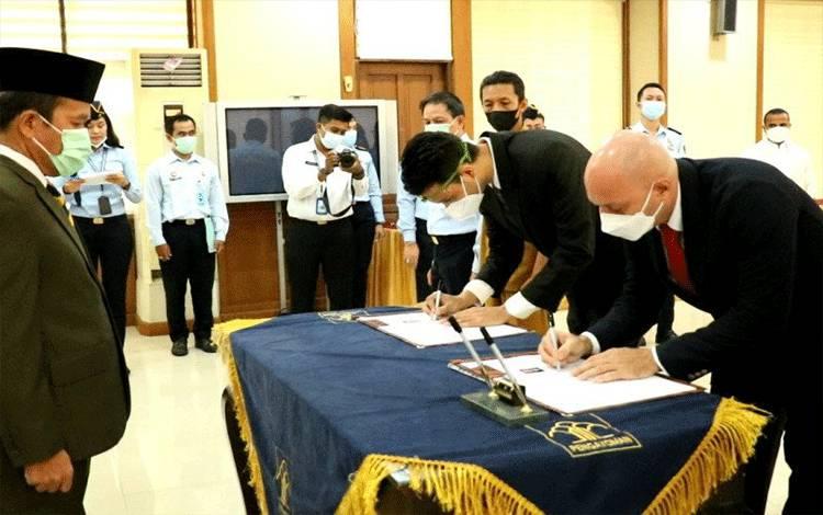 Saat kedua WNA melakukan penandatanganan berita acara Pengambilan Sumpah Kewarganegaraan, di Kantor KemenkumHAM Bali, Denpasar, Bali, Senin (22/03/2021). ANTARA/HO-Humas KemenkumHAM Bali. (Antara/Ayu Khania Pranisitha/2021)