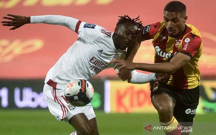 Penyerang Olympique Lyon Karl Toko Ekambi (kiri) berebut penguasaan bola dengan bek RC Lens Loic Bade dalam lanjutan Liga Prancis di Stadion Felix Bollaert-Dellelis, Lens, Prancis, Sabtu (3/4/2021) waktu setempat