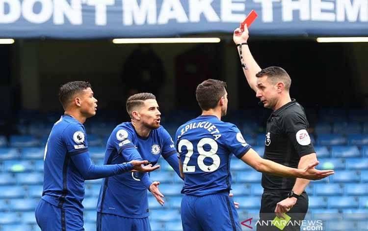 Wasit David Coote (kanan) memperlihatkan kartu merah kepada bek Chelsea Thiago Silva (kiri) dalam lanjutan Liga Inggris melawan West Bromwich Albion di Stadion Stamford Bridge, London, Inggris, Sabtu (3/4/2021)