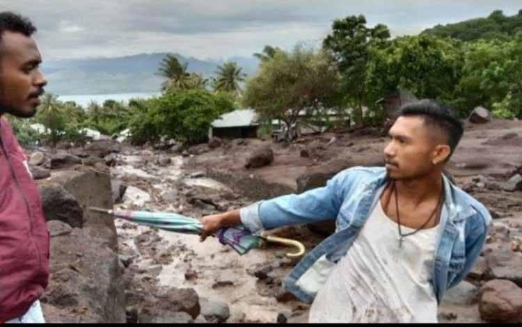 Dua pemuda sedang membantu pencarian korban banjir dan longsir yang menerjang Desa Nele Lamadike, Kecamatan Ile Boleng, Kabupaten Flores Timur, Nusa Tenggara Timur (NTT) pada Minggu (4/4/2021)