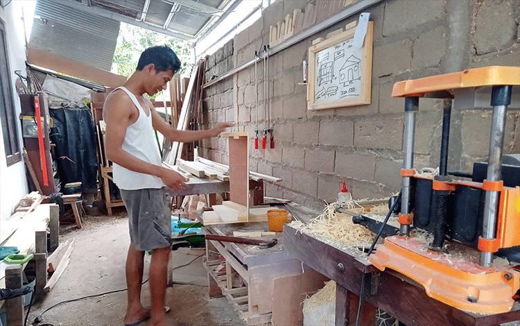 Hengki (29) warga RT 17 Kelurahan Tamiang Layang Kabupaten Barito Timur saat mengerjakan pesanan konsumennya.