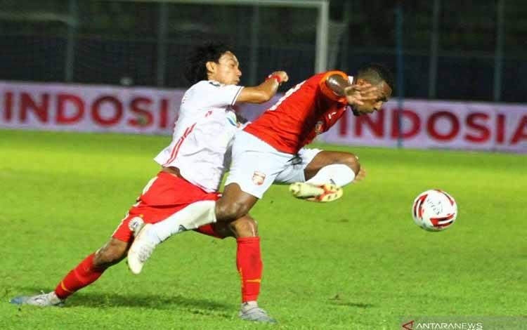 Pesepak bola Persija Jakarta Novri Setiawan (kiri) berusaha menghentikan laju pesepak bola Borneo FC Samarinda, Terens Owang Priska (kanan) dalam pertandingan Piala Menpora Grup B di Stadion Kanjuruhan, Malang, Jawa Timur, Sabtu (27/3/2021)