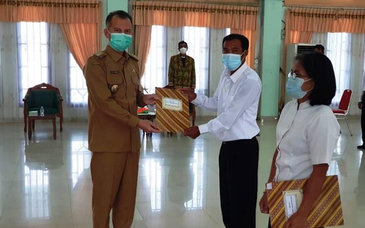 Bupati Gumas Jaya S Monong (kiri) menyerahkan SK pengangkatan kepada perwakilan PPPK.