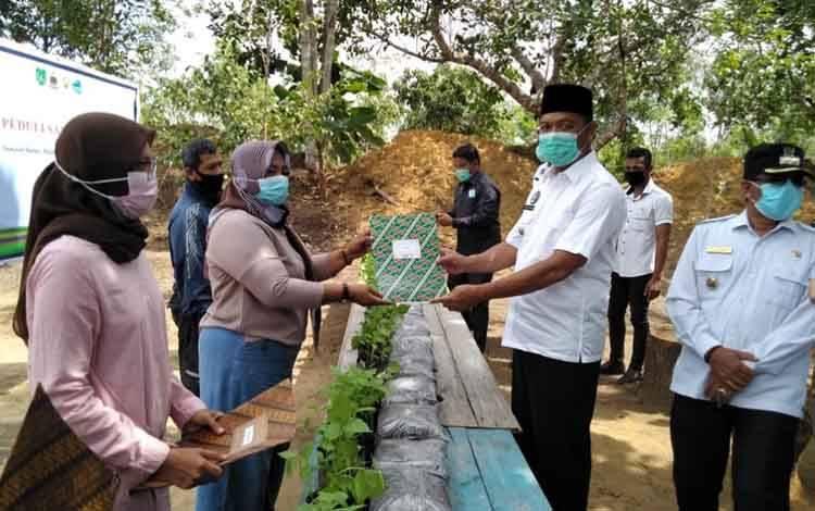 Bupati Sukamara, Windu Sibagio saat memberikan bantuan bibit tanaman dan kompos kepada masyarakat.