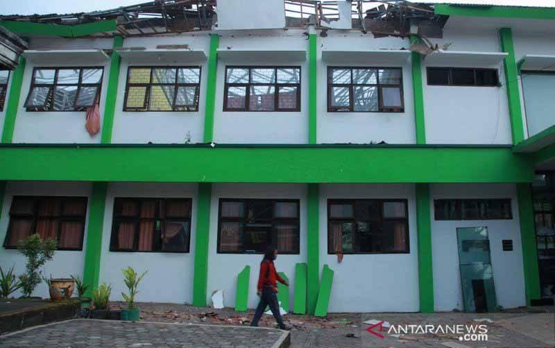 Seorang warga melintas di depan bangunan sekolah yang rusak akibat gempa di SMK Negeri 1 Turen, Malang, Jawa Timur, Sabtu (10/4/2021). (foto : ANTARA FOTO/Bayu/aww)
