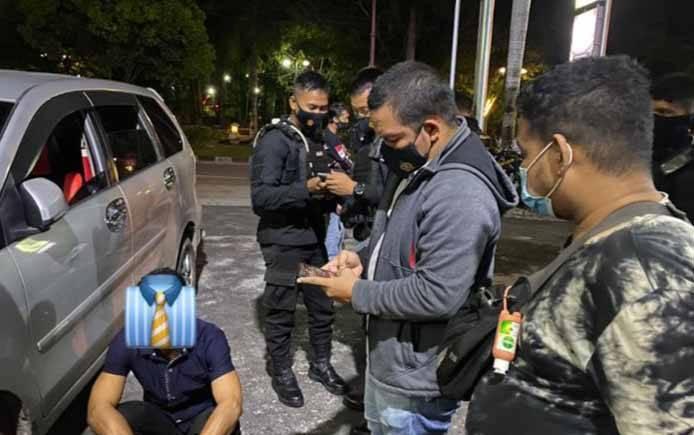 Wakil Direktur Ditsamapta Polda Kalteng, AKBP Timbul RK Siregar saat menginterogasi pasangan pria yang terpergok di kawasan Stadion Sanaman Mantikei, Sabtu malam, 10 April 2021.