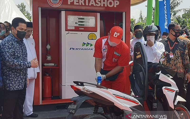 Menteri BUMN Erick Thohir (kiri) dan Habib Muhammad Luthfi bin Ali bin Yahya (dua dari kiri) saat menyaksikan pengisian perdana BBM jenis Pertamax ke dalam tangki sepeda motor di Pertashop Pondok Pesantren Nurul Quran, Desa Surusunda, Kecamatan Karangpucung, Kabupaten Cilacap, Minggu (11/4/2021). (foto : ANTARA/Sumarwoto)