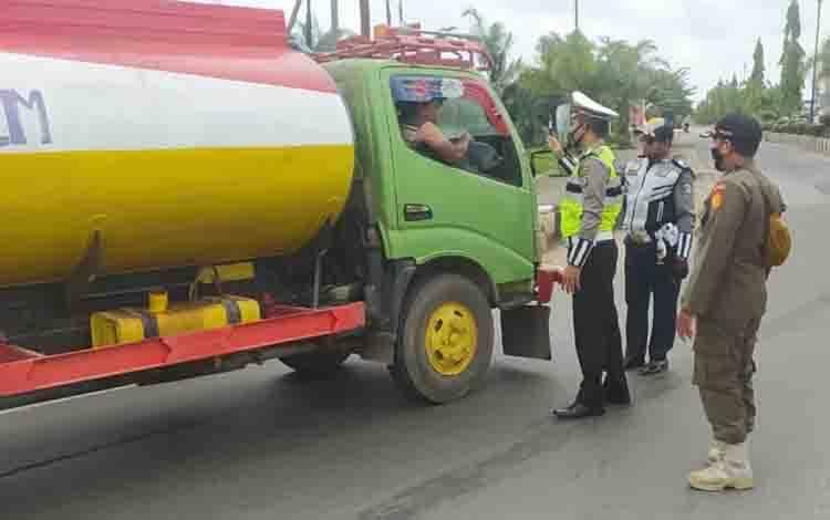Sebuah truk CPO saat hendak melintas masuk ke jalan kota, namun diberhentikan karena sudah dilarang