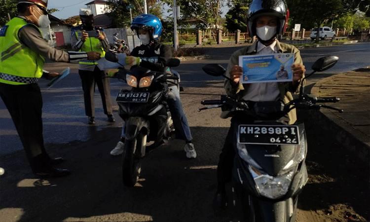 Satlantas Polres Seruyan mengajak masyarakat cegah Covid-19 dan selalu tertib berlalu lintas dengan membagikan brosur dan stiker.