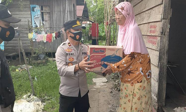 Kapolsek Seruyan Hilir Ipda Fahroni menyerahkan paket sembako kepada salah satu warga yang membutuhkan di Kuala Pembuang.