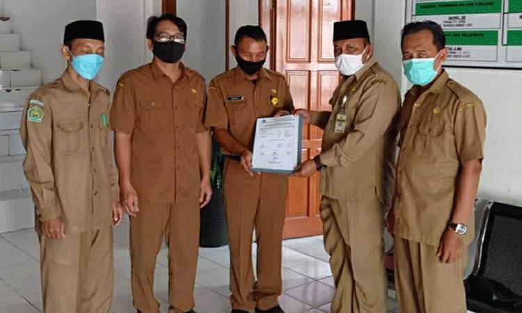 Kasi Bimas Islam Kemenag Kapuas, M Poteran Sosilo saat menyerahkan berita acara pengukuran arah kiblat pembangunan musala di Bappeda Kapuas.