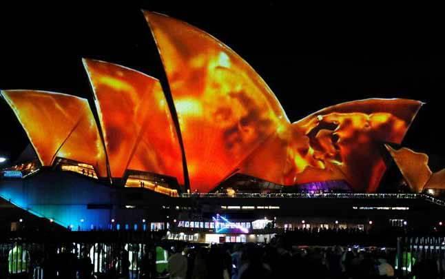 Pengunjung melihat proyeksi di layar Opera House Sydney saat berlangsungnya Vivid Sydney, sebuah festival cahaya, dan musik di Sydney, Australia, 25 Mei 2018. Festival akan berlangsung selama 23 hari. (foto : REUTERS/David Gray)