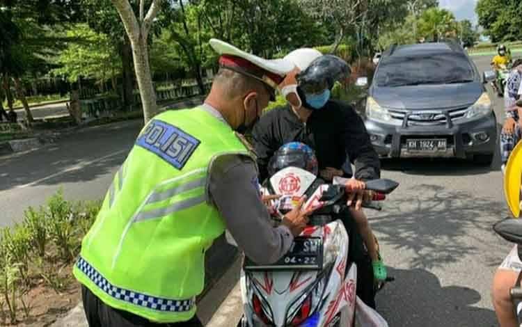 Personel Satlantas Polres Kapuas saat membagikan stiker kepada pengendara melintas di Kota Kuala Kapuas.