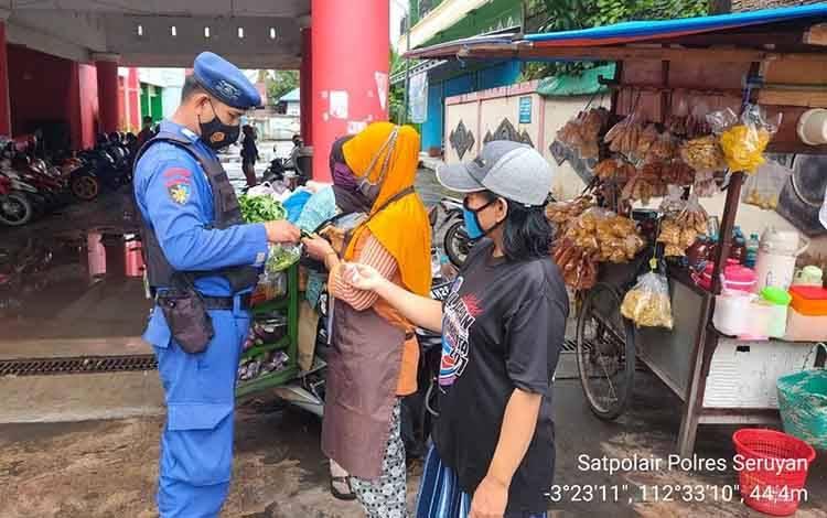 Personel Polairud Polres Seruyan saat membagikan masker sambil memberikan pesan kamtibmas kepada warga di kawasan Pasar Kuala Pembuang