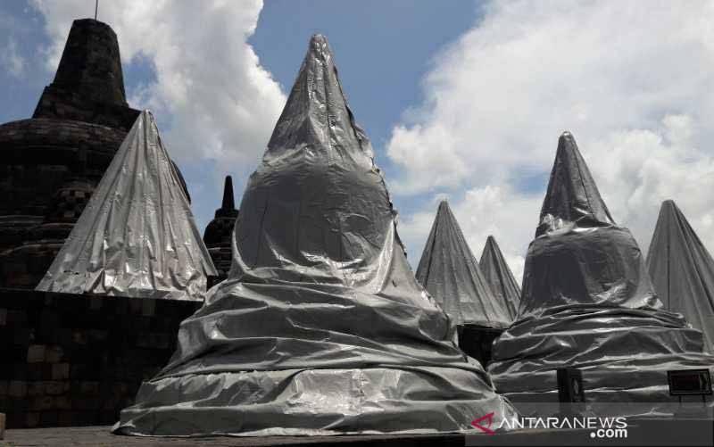 Stupa Candi Borobudur di Kabupaten Magelang, Jawa Tengah, Minggu (18/4/2021) masih ditutup terpaulin untuk mengantisipasi ancaman abu erupsi Gunung Merapi. (foto : ANTARA/Heru Suyitno)