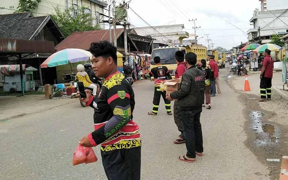 Anggota BPK Samuja Ampah saat membagikan takjil bagi pengguna jalan yang melintas depan posko.
