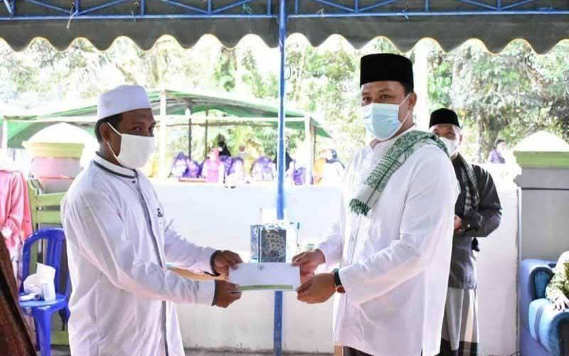Bupati Lamandau Hendra Lesmana (kanan) menyerahkan bantuan di sela safari Ramadhan di Desa Suja, Kecamatan Lamandau. (foto : ANTARA/HO-Pemkab Lamandau)