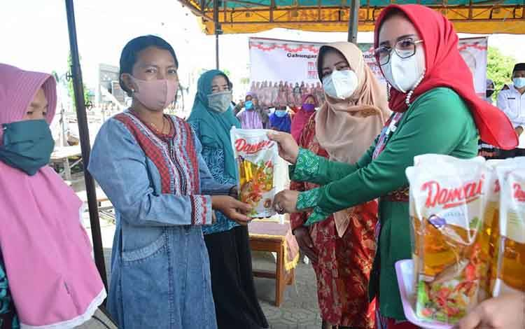 Ketua GOW Seruyan, Iswanti menyerahkan minyak goreng kepada perwakilan masyarakat pada kegiatan pasar murah ramadhan menyambut Hari Kartini