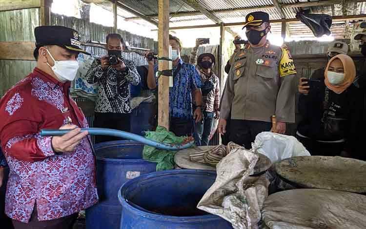 Bupati Kotim, Halikinnor saat melihat proses permentasi pembuatan arak putih, di lokasi pabrik miras yang mereka bongkar.