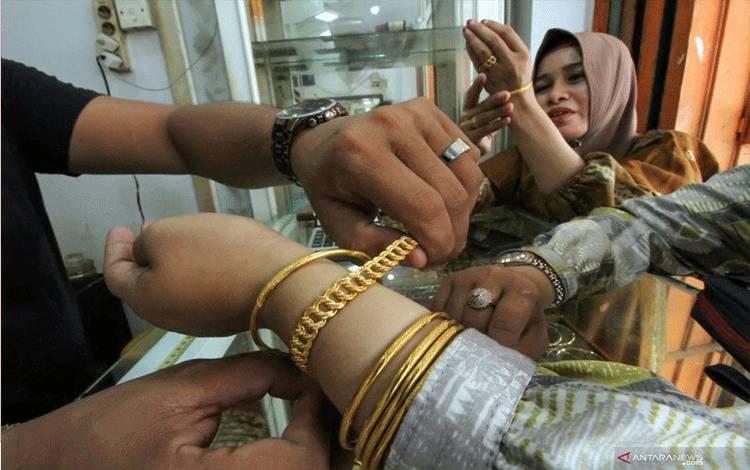 Pedagang melayani pembeli di pusat penjualan emas London Kota Lhokseumawe, Aceh, Kamis (21-4-2021). Harga emas murni di tempat tersebut naik dari Rp750 ribu per gram menjadi Rp794 ribu per gram. ANTARA FOTO/Rahmad/aww.