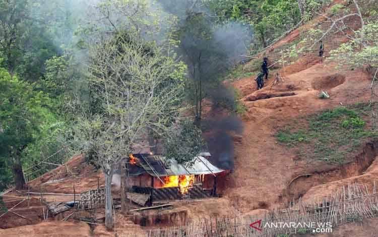 Pasukan etnis minoritas Karen terlihat setelah membakar sebuah bangunan di dalam pos militer Myanmar dekat perbatasan Thailand, yang terlihat dari sisi Thailand di Thanlwin, juga dikenal sebagai Salween, tepi sungai di provinsi Mae Hong Son, Thailand, Rabu (28/4/2021)
