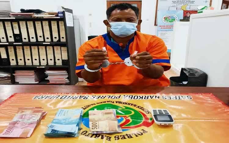 Tersangka Cibung beserta barang bukti saat diamankan di Polres Barito Utara