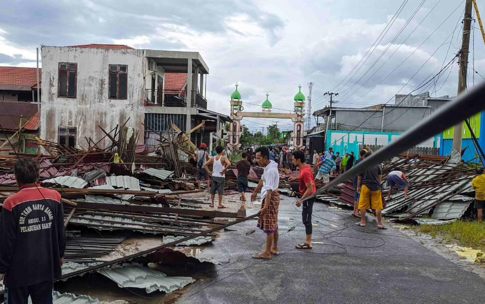 Sejumlah warga saat membersihkan bangunan roboh yang menutup jalan.