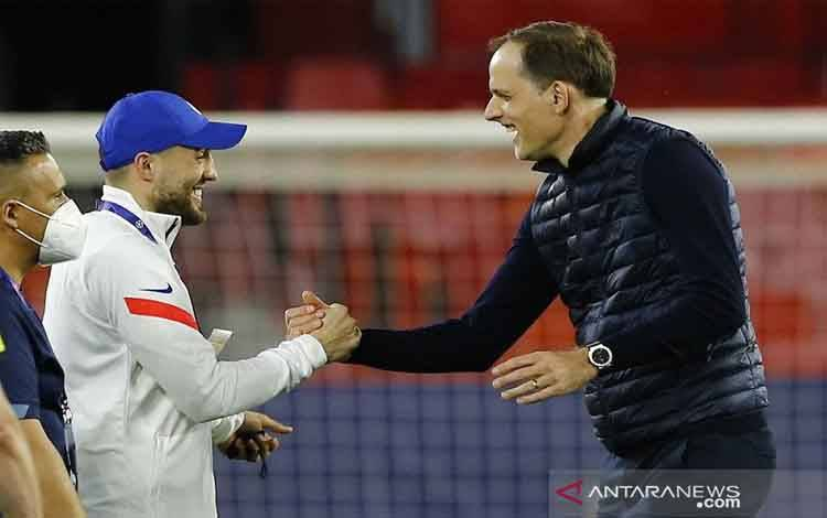 Manajer Chelsea Thomas Tuchel (kanan) menyalami gelandang Mateo Kovacic seusai timnya lolos ke semifinal Liga Champions walau kalah 0-1 dari Porto dalam leg kedua perempat final di Stadion Ramon Sanchez Pizjuan, Sevilla, Spanyol, Selasa (13/4/2021)