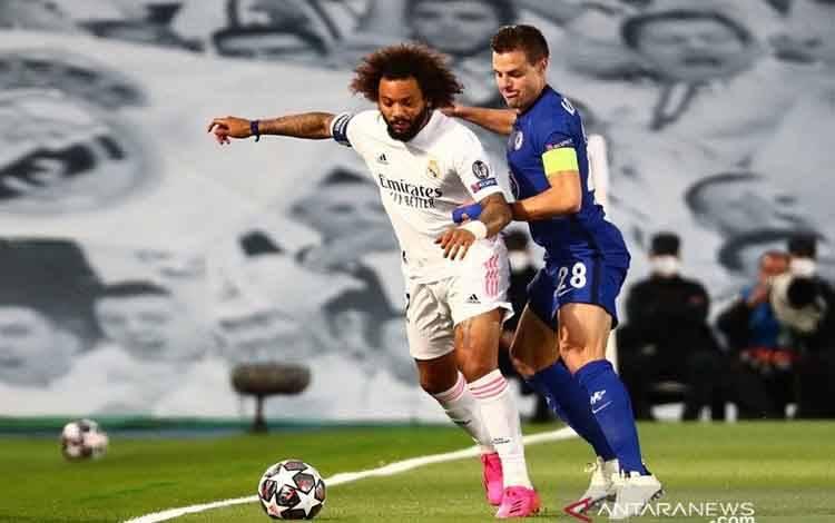 Bek Real Madrid Marcelo (kiri) berebut bola dengan kapten Chelsea Cesar Azpilicueta dalam leg pertama semifinal Liga Champions di Stadion Alfredo Di Stefano, Madrid, Selasa (27/4/2021)