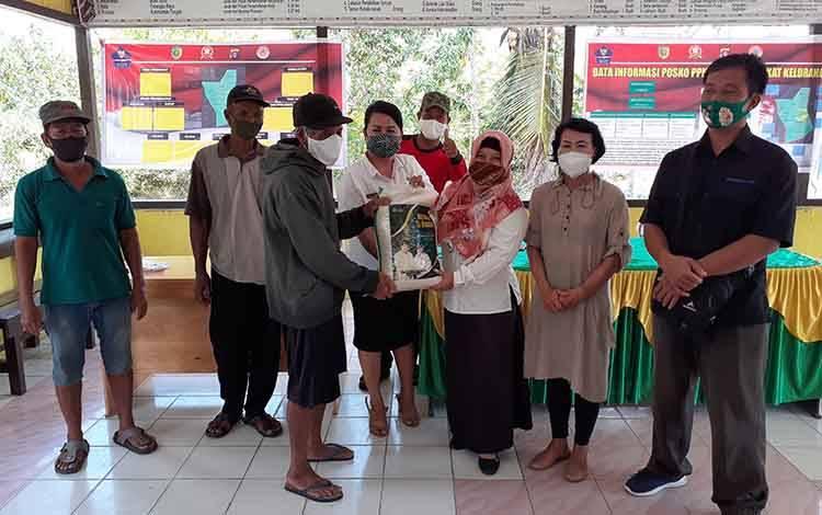 Lurah Marang, Yulianti saat menyerahkan secara simbolis beras zakat H Abdul Rasyid AS kepada salah satu lansia yang ada di wilayah setempat.