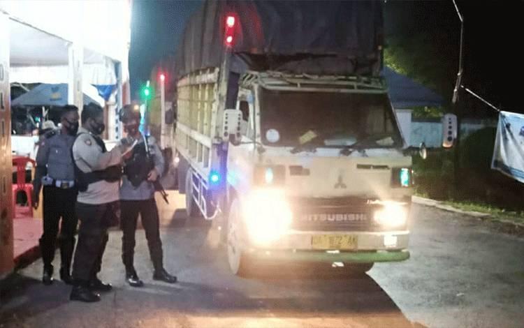 Petugas Pos Penyekatan Perbatasan Kalteng - Kalsel di Jalan Trans Kalimantan KM 12,5 Kecamatan Kapuas Timur memeriksa dokumen sopir angkutan.