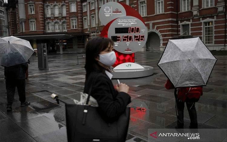Seorang perempuan dengan masker di wajahnya berjalan di depan jam penghitung mundur 100 hari menjelang Olimpiade Tokyo 2020 di Tokyo, Jepang, Rabu (14/4/2021). Olimpiade Tokyo 2020 tertunda hingga tahun 2021 akibat pandemi COVID-19. (ANTARA FOTO/REUTERS/Issei Kato/wsj.)