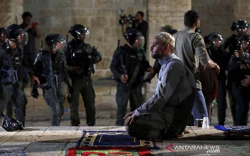 Seorang warga Palestina berdoa sementara polisi Israel berkumpul setelah bentrokan di kompleks Masjid Al Aqsa, di  Yerusalem, (7/5/2021). Bentrokan tersebut imbas ketegangan di Yerusalem yang meningkat karena warga Palestina memprotes pembatasan akses Israel ke beberapa bagian Kota Tua Yerusalem selama bulan suci Ramadhan dan beberapa keluarga Palestina diperintahkan untuk meninggalkan rumah mereka, untuk memberi jalan bagi pemukim Israel. (foto : ANTARA FOTO/REUTERS / Ammar Awad/aww.)