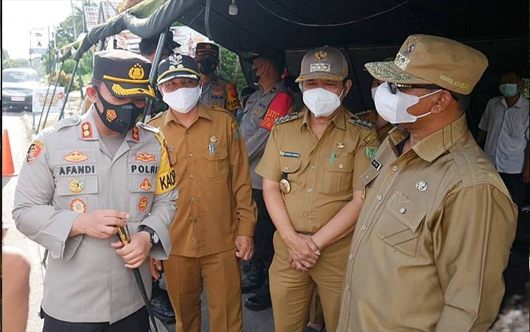 Wagub Kalteng, Habib Ismail bin Yahya (paling kanan) sedang menyimak penjelasan Kapolres Barito Timur di pos penyekatan perbatasan Kalteng - Kalsel di Pasar Panas.