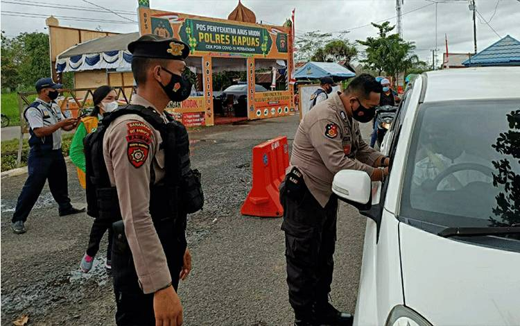 Petugas pos penyekatan arus mudik saat mengecek kelengkapan dokumen pengendara di Kecamatan Kapuas Timur.