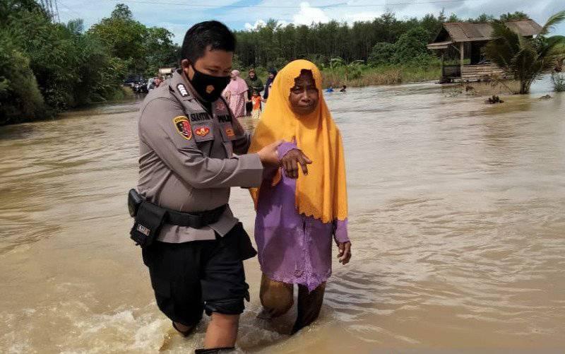 Anggota Polsek Satui, Polres Tanah Bumbu melakukan evakuasi terhadap warga terdampak banjir. (foto : ANTARA/Firman)