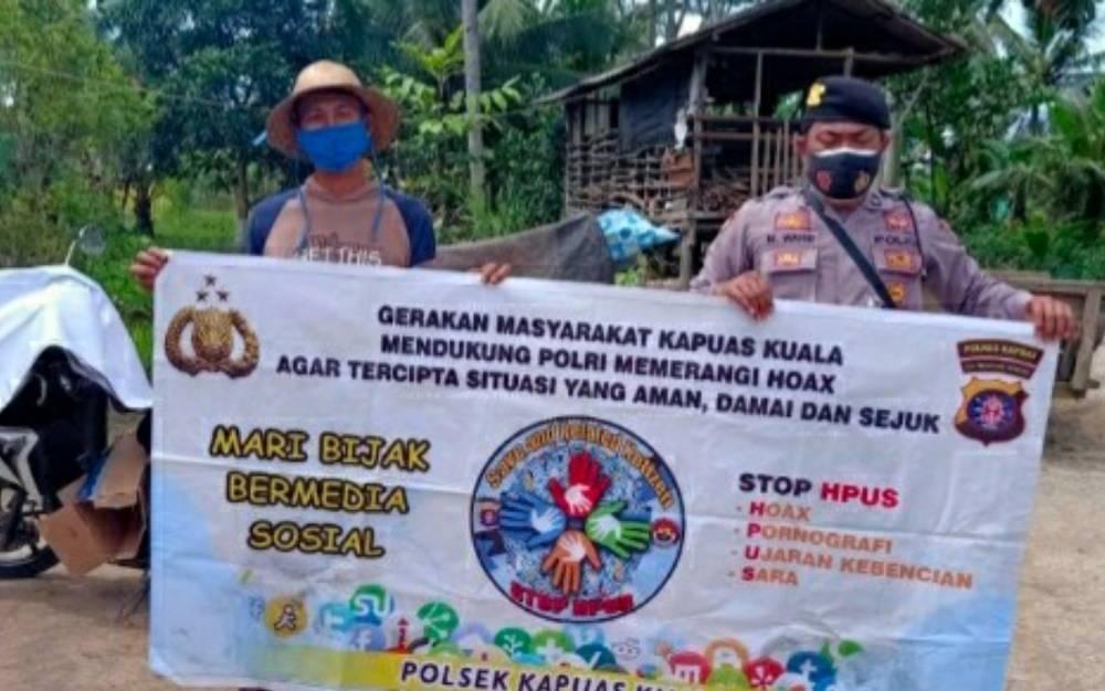 Personel Polsek Kapuas Kuala saat menyosialisasikan agar warga bijak dalam menggunakan medsos, Sabtu, 13 Mei 2021.