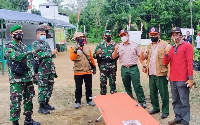 Kepala Pelaksana BPBD Damkar Barito Timur, Riza Rahmadi (dua dari kanan) saat menyerahkan bantuan di pos PPKM Mikro Desa Simpang Naneng.