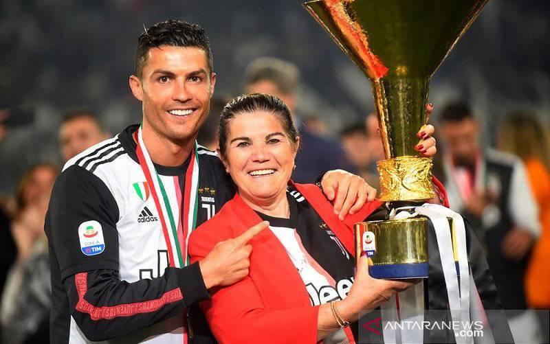 Megabintang Juventus Cristiano Ronaldo (kiri) berpose bersama ibunya Dolores Aveiro dan trofi Liga Italia Serie A saat selebrasi di Stadion Allianz, Turin, Italia, pada 19 Mei 2019. (foto : ANTARA/REUTERS/Massimo Pinca)