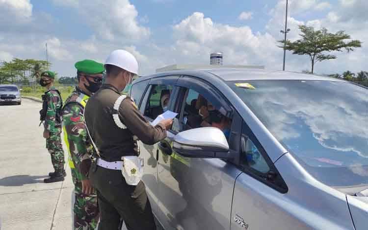 etugas Gabungan dari TNI/Polri serta Dinas Perhubungan sedang memberhentikan kendaraan yang ingin menuju ke Bandarlampung maupun Pulau Jawa di 'Rest Area' KM 87 B di Jalan Tol Trans Sumatra (JTTS) untuk di periksa surat bebas COVID-19 baik dengan 'Rapid Test' Antigen, 'PCR' dan juga GeNose. Minggu, (16/5/2021)