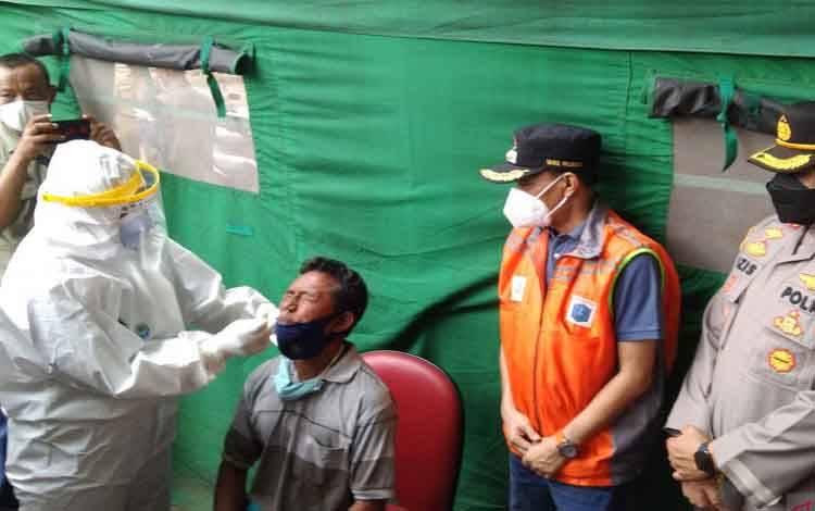 Petugas medis melakukan tes usap antigen kepada seorang warga setelah kembali ke Jakarta usai mudik serangkaian Idul Fitri 1442 Hijriah di Duren Tiga, Pancoran, Jakarta Selatan, Minggu (16/5/2021)
