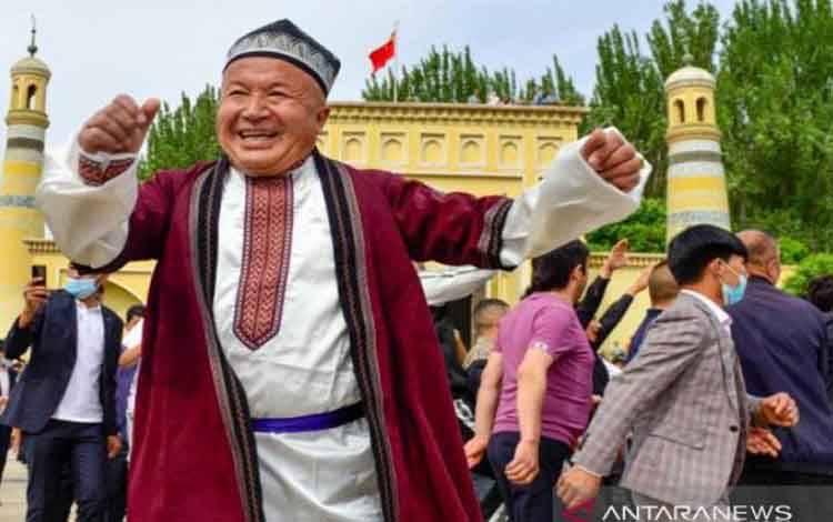 Warga etnis minoritas Muslim Uighur menari bersama merayakan Idul Fitri di halaman Masjid Idkah, Kota Kashgar, Daerah Otonomi Xinjiang, China, pada Kamis (13/5/2021)