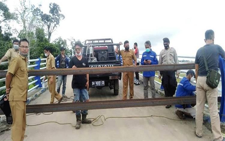Kepala Dinas PUPR Barito Utara M Iman Topik didampingi Kepala Bidang Bina Marga Dedi dan personel Polsek Teweh Tengah serta pekerja las melakukan pengelasan besi di jalan pintu masuk ke jembatan, Senin (17/5/2021).ANTARA/HO-Dinas PUPR Barut