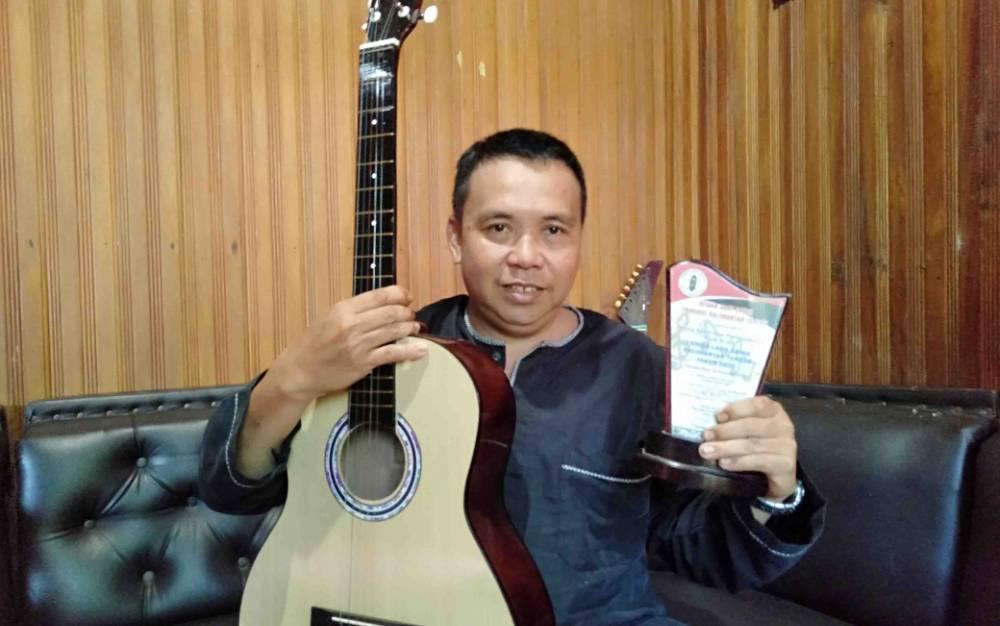 Shogy, pencipta lagu daerah Dayak asal Desa Petak Bahandang Katingan memegang gitar dan penghargaan yang diberikan DAD Kalteng